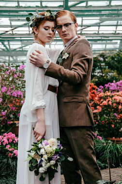 portrait of stylish bride and groom hugging each other in greenhouse