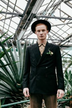 portrait of handsome red hair man in hat looking at camera in greenhouse
