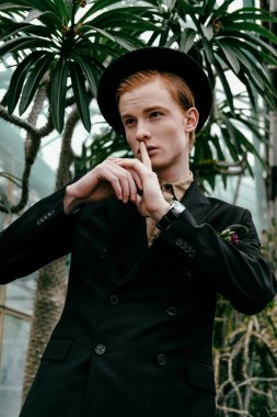 portrait of stylish young red hair man in hat showing silence sign in glasshouse