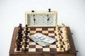 Orologio per scacchi vicino a scacchiera con figure e banconote del dollaro isolate su bianco