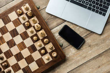 Smartphone, laptop and chess board with chess pieces on wooden surface