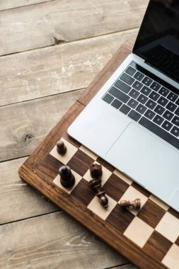 Cropped image of chess board with chess pieces and laptop on rustic wooden surface