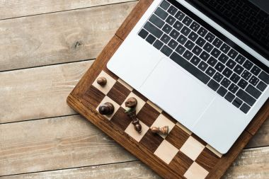 Top view of chess board, laptop and chess pieces on rustic wooden surface