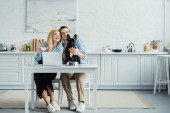 Photo Smiling couple with coffee sitting by table with laptop in kitchen and stroking Frenchie dog
