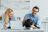 Fotografie Lächelnde paar Fütterung ihres Hundes Frenchie am Küchentisch mit laptop
