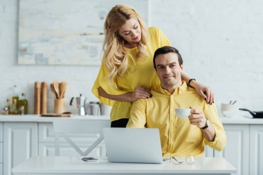 Girlfriend standing by man drinking coffee and working on laptop in kitchen