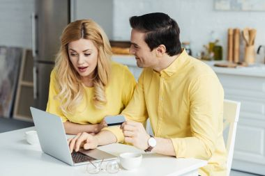 Man and woman drinking coffee and shopping online by laptop