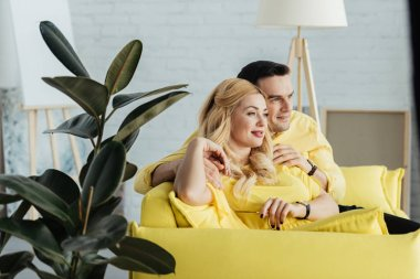 Pretty couple sitting on yellow sofa in light room