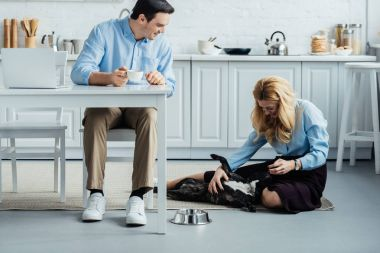 Smiling man with coffee by table with laptop in kitchen and blonde woman stroking Frenchie dog