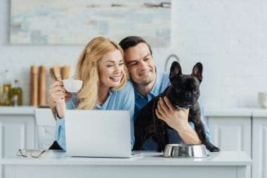 Man and woman drinking coffee and hugging their dog on kitchen table with laptop