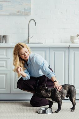 Smiling blonde woman stroking frenchie dog on kitchen floor