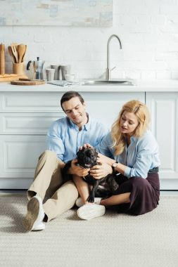 Happy man and blonde woman sitting on floor in kitchen with French bulldog