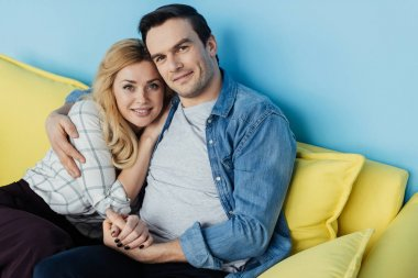 Embracing man and woman sitting and holding hands on yellow sofa