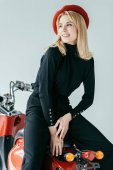 Photo Attractive young woman in red beret posing by vintage scooter isolated on grey