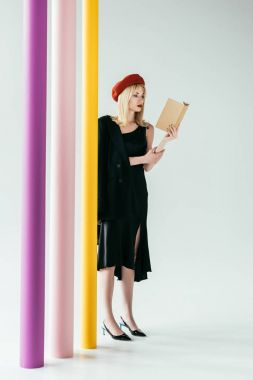 Stylish pretty woman in black dress reading book by colorful columns
