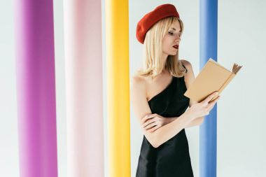 Attractive young woman in black dress reading book by colorful columns isolated on grey