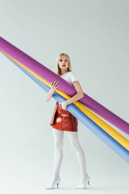 Attractive young woman carrying colorful paper rolls