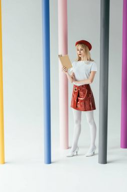 Attractive young woman reading book and posing by colorful pillars
