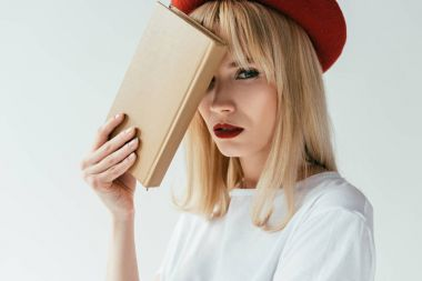 Fashionable blonde girl with red lips holding book isolated on grey