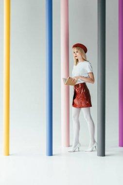 Stylish pretty woman posing by colorful pillars