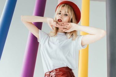 Elegant blonde girl posing by colorful pillars isolated on grey