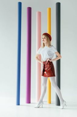 Elegant blonde girl in vintage style clothes in front of colorful columns