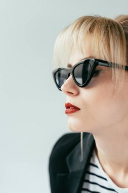 Elegant blonde girl in sunglasses with red lips isolated on grey