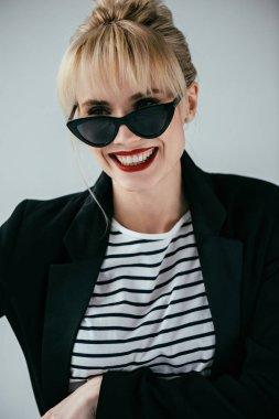 Stylish pretty woman wearing retro sunglasses isolated on grey
