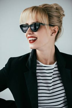 Smiling blonde girl wearing retro sunglasses isolated on grey