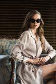 Fotografia bella donna in occhiali da sole e trench in posa in poltrona