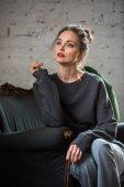 atraktivní brunetka žena v módní svetr sedí na křesle a hledat dál