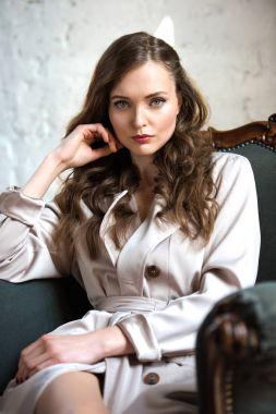 beautiful woman in beige trench coat sitting in armchair