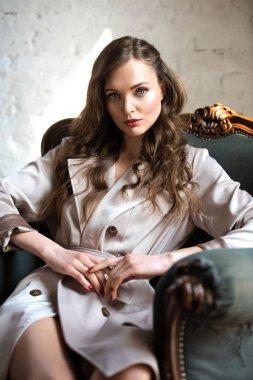 attractive woman in beige trench coat sitting in armchair