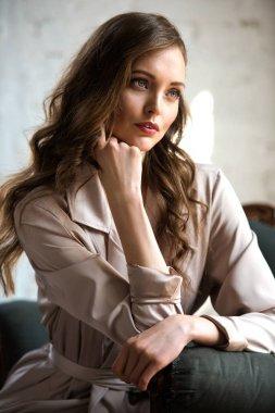 Brunette woman with long hair in beige trench coat posing in armchair stock vector