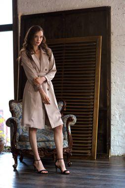 beauty in classic beige trench coat posing near armchair