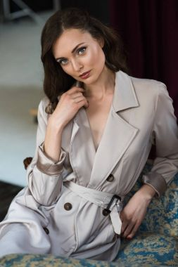 attractive woman in trench coat sitting in armchair