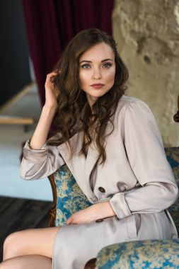 elegant woman in fashionable trench coat sitting in armchair