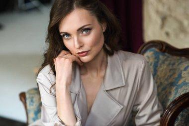 portrait of elegant lady in beige trench coat sitting in armchair