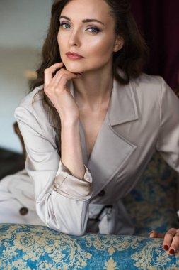 beautiful woman in elegant trench coat sitting in armchair