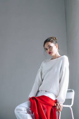 beautiful young woman in trendy white clothes sitting and looking at camera on grey