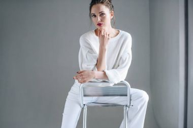 portrait of beautiful brunette woman in trendy white clothes sitting on chair and looking at camera on grey