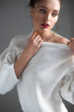 beautiful brunette woman wearing white sweater and looking away on grey