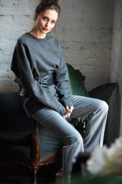 beautiful young woman in trendy grey clothes sitting on armchair and looking at camera