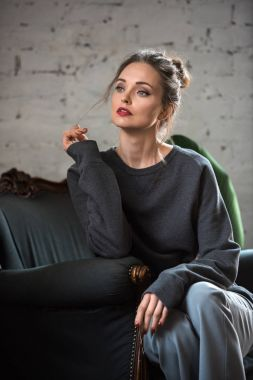 attractive brunette woman in trendy jumper sitting on armchair and looking away