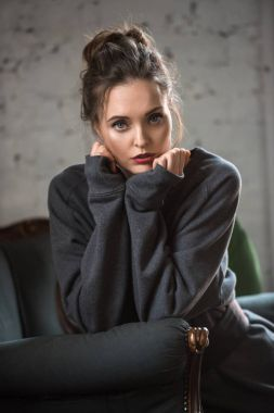 portrait of beautiful brunette woman in trendy sweater sitting on armchair and looking at camera