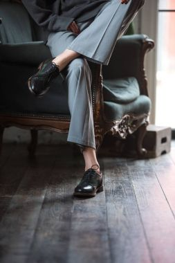low section of girl in leather shoes and stylish pants sitting on armchair