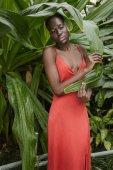krásná africká americká žena pózuje v červených šatech v tropické zahradě