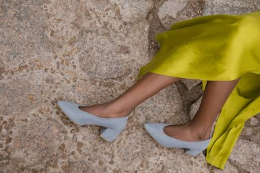 cropped view of woman in elegant yellow dress and grey heels on pavement