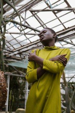 fashionable sensual african american girl posing in greenhouse