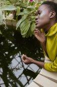 Krásná módní africká americká dívka s třpytky make-up pózuje u bazénu